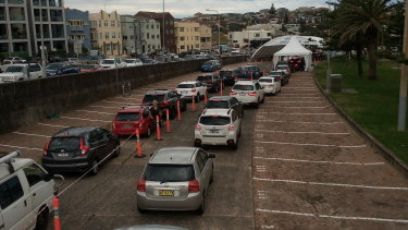 Cars queue up in the car park and the street at the Bondi Beach COVID testing centre on Friday.