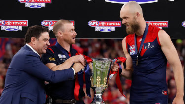 Garry Lyon presents the premiership cup to Simon Goodwin and Max Gawn.