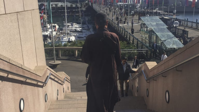 A fake Buddhist monk approaches people for money in Darling Harbour.