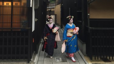 The two geisha leave a laneway in Kyoto.