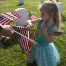On Memorial Day weekend Samara Reiseweber 2, helps her father  Lieutenant-Colonel Andrew Reisenweber place flags at graves in Hampton, Virginia.