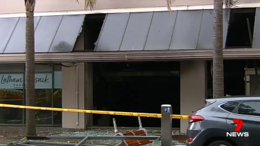 Glass is left shattered on the ground outside a shop beneath an apartment block following the explosion.