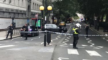 Police activity on Millbank, in central London, after a car crashed into security barriers outside the Houses of Parliament.