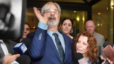 An animated John Jarratt celebrates his not guilty verdict on Friday, alongside his wife Rosa Miano.