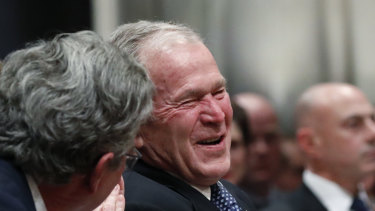 Former president George W. Bush smiles with his brother Jeb Bush at the state funeral for their father, former president George H.W. Bush.