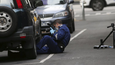 A forensics officer takes photos of a car parked in Anthony Street.