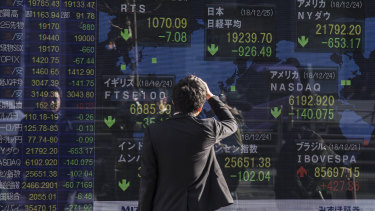 A man looks at an electronic stock board outside a securities firm in Tokyo. The Nikkei 225 index entered bear market territory, as Japanese stocks headed for their worst December on record.