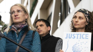 """Sarah Kuhnen is teary-eyed and Jenelle Masterson holds a sign reading """"Justice for Justine"""" outside the courtroom."""