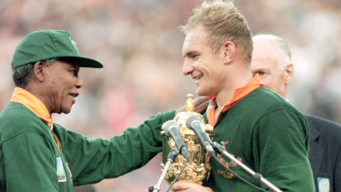 Nelson Mandela hands South African captain Francois Pienaar the Webb Ellis Trophy.