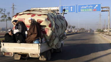A family with their goods loaded on a truck drives fleeing Idlib province. The UN says that some 60,000 Idlib residents have been displaced in recent weeks by a Russia-backed government offensive.