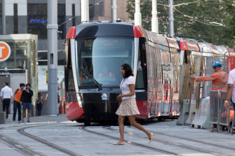 A pedestrian crosses in front of a tram on George Street last week.