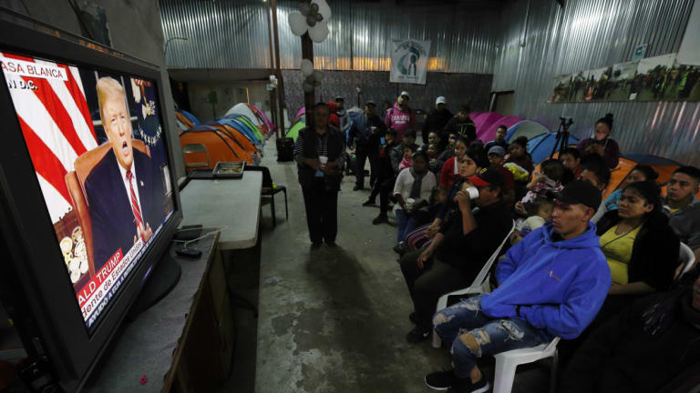 Migrants mainly from Mexico and Central America look on as US President Donald Trump gives his prime-time address about border security, watching from a border migrant shelter in Tijuana, Mexico.