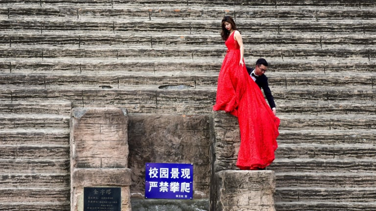 A couple climb on a replica of an Egyptian pyramid as they pose for wedding photos in Chengdu in China's south-western Sichuan province.