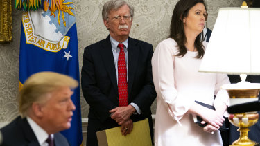 US President Donald Trump (left) and National Security Adviser John Bolton with Sarah Sanders in the Oval Office.