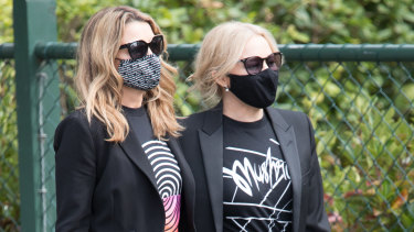 Sisters Dannii and Kylie Minogue arrive to pay their respects to the Mushroom Group founder, who was a close friend.