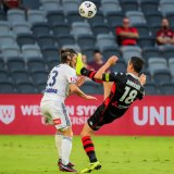 Victory's Marco Rojas is caught high byWanderers skipper Graham Dorrans.