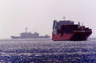 An Australian navy ship passes by the MV Tampa off Christmas Island.
