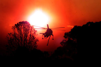 The helicopter, dubbed Elvis, working against in a blood-red sky in Macquarie Park.