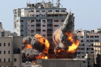 A ball of fire erupts from a media building in Gaza City after an Israeli airstrike.