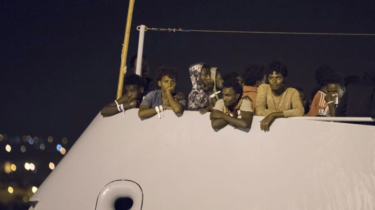 """Migrants wait to disembark from Frontex ship """"Protector"""" at the port of Pozzallo, Sicily, Italy, after a half-dozen European countries promised to take some of them."""