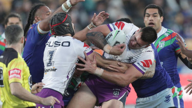 Three's a crowd: The Warriors gets to grips with Nelson Asofa Solomona of the Storm at Mt Smart Stadium.
