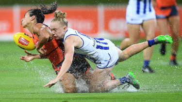 Wet and wild: Amanda Farrugia of the Giants is tackled by Emma Humphries of the Kangaroos.