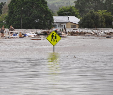 A young Toowoomba couple desperately cross the Grantham rail line as floodwaters rise on January 10, 2011.