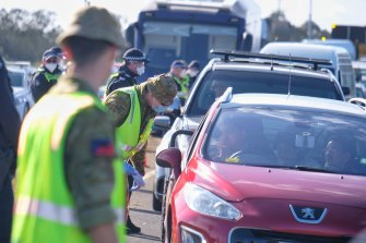 Members of the Australian Defence Force and Victoria Police at a vehicle checkpoint along the Princes Freeway near Little River to enforce metro Melbourne lockdown restrictions on Monday.
