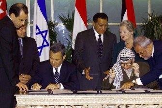 Palestinian leader Yasser Arafat, seated right, consults with Saeb Erekat, right, as Israeli Prime Minister Ehud Barak, seated left, sign the Sharm El-Sheikh Memorandum in 1999.