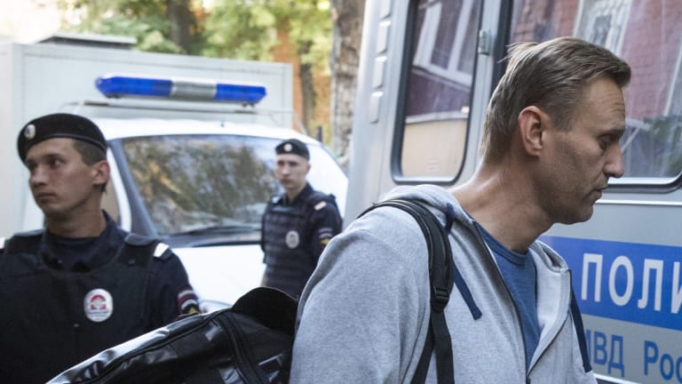Russian opposition leader Alexei Navalny, right, leaves a court for jail surrounded by police officers in Moscow, Russia.