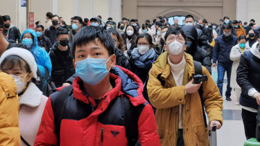 People wear face masks as they wait at Hankou Railway Station in Wuhan last week.
