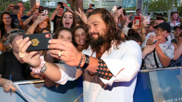 Jason Momoa takes selfies with the crowd behind him at the Australian  premiere of Aquaman on the Gold Coast on Tuesday.