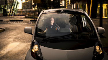 Electric car owner Daryl Budgeon in his 2012 Misubishi i-Miev,