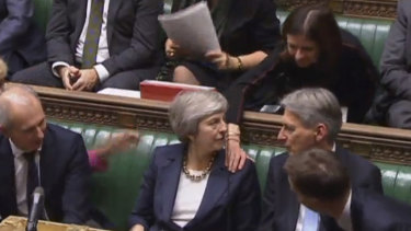 Theresa May is congratulated by Conservative Party ministers in the House of Commons after speaking at the start of a five-day debate on Brexit.