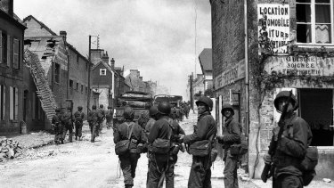 American paratroops patrol in the streets of Sainte-Mere-Eglise, France, before pushing on toward Cherbourg.  June 1944.