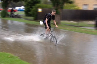 A cyclist rides through a flooded street in Corio, near Geelong, this afternoon.
