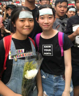 Heather and Ariel carried white flowers in memory of the protester who died in Hong Kong on Saturday.