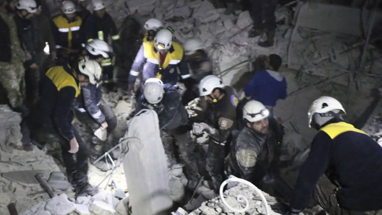Syrian Civil Defence White Helmets inspect a damaged building after an attack in July.