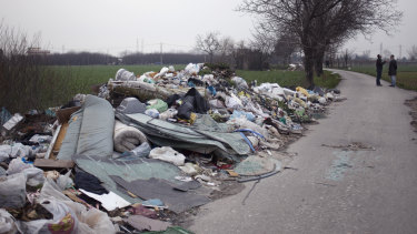 Environmental activists Leopoldo Esposito and Ciro Tufano survey farmland littered with a mix of household and industrial waste near Marigliano, north of Naples in Italy, in 2014.