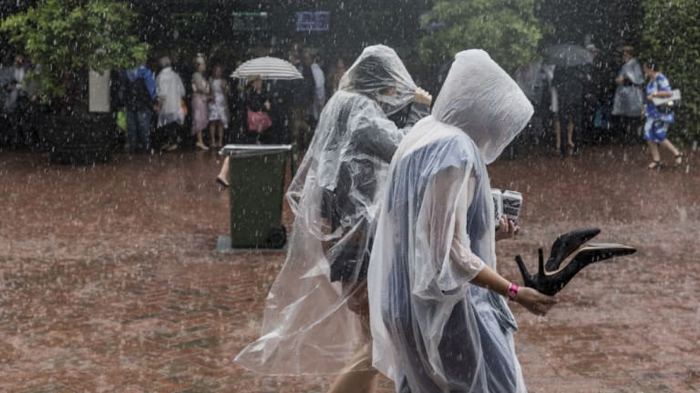 Thousands of racegoers faced torrential rain for the start of the Melbourne Cup races.