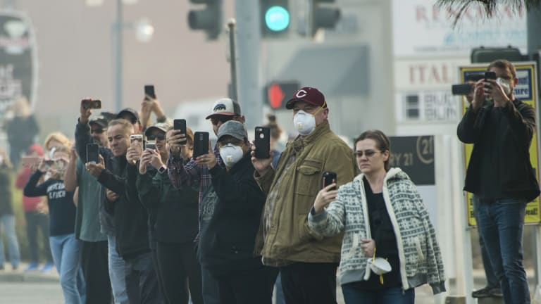 Residents wave to a motorcade during President Donald Trump's visit of the Camp Fire in Chico, California.