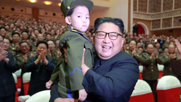 North Korean leader Kim Jong-un holds a boy during a musical performance in this photo provided by the North Korean government.