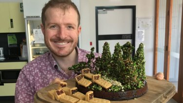 Dr Matthew Holden with a cake he baked to reflect his conservation burial research.