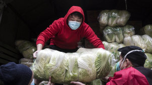 Employees wear protective masks while carrying vegetables from trucks at a hospital in Wuhan.
