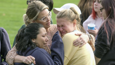 Students are comforted as they wait to be reunited with their parents following the shooting.