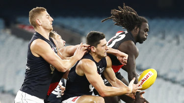 In the thick of it: Carlton's Marc Pittonet scraps in the pack against Bomber Anthony McDonald-Tipungwutii.