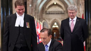 Then-Australian prime minister Tony Abbott signs the guest book as then-Canadian prime minister  Stephen Harper, right, and then Speaker of the House of Commons Andrew Scheer watch on, at Parliament Hill in Ottawa, Ontario, in June 2014.