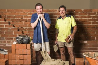 Artist Mitch Cairns building a red brick wall with his bricklayer father, David, at Carriageworks.