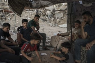 Palestinians sit inside a makeshift tent they built in the rubble of their home, destroyed by an air strike in Beit Lahia, in the northern Gaza Strip, in June.