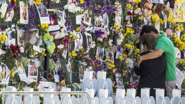 People mourn at the memorial wall for the victims of the Champlain Towers South collapse in Surfside, Florida.